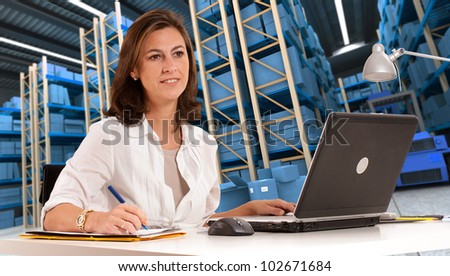 Female administrative in a desk with a distribution warehouse in the background - stock photo