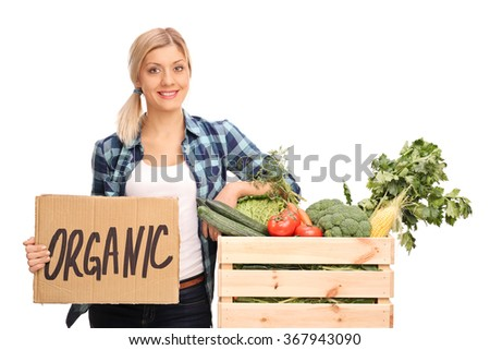 Female agricultural worker holding a cardboard sign that says organic and leaning on a crate full of vegetables isolated on white background - stock photo