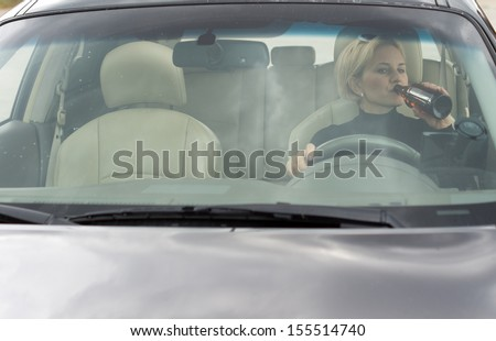 Female alcoholic sitting in her car drinking and driving as she gulps alcohol directly from the bottle, view through the front windscreen - stock photo