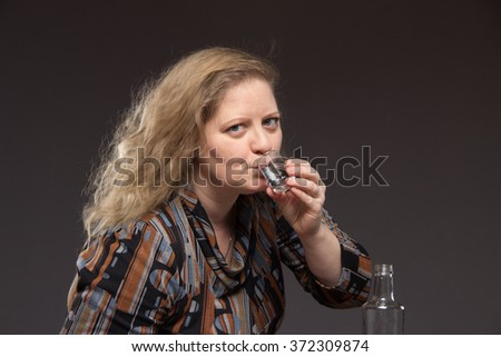 Female alcoholism. Woman aged one drinks vodka from a bottle