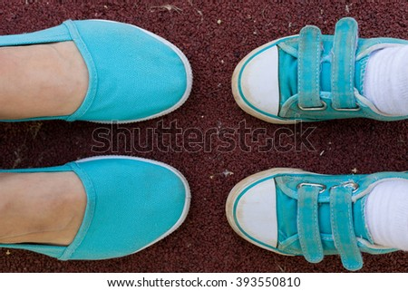 Female and child's feet in sports turquoise shoes. Sneakers are on the ground in a park close-up. Together. Family. Mother and son walking in the park. - stock photo