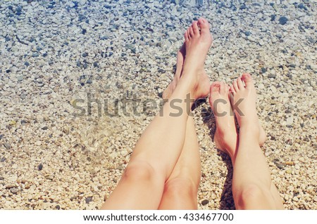 Female and children's feet on a beach against the sea in a summer sunny day. Family holiday. Family rest - stock photo