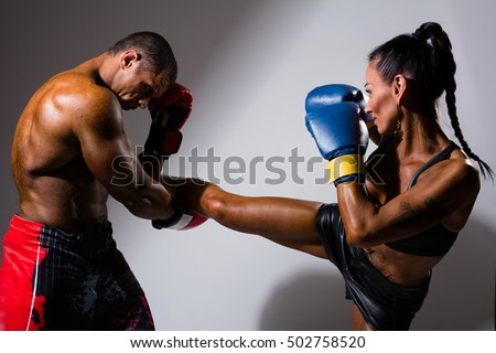 Female and male boxers with boxing gloves during a match, isolated on studio