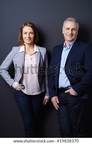 Female and male business partners stand together resting casually against a dark blue background and smile - stock photo