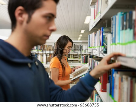 female and male college students taking textbook from shelf in library. Horizontal shape, side view, waist up, focus on background