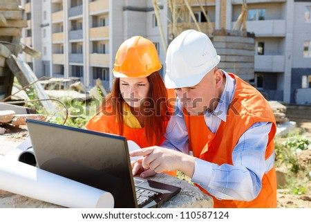 female and male construction workers looking at laptop against the backdrop of houses under construction - stock photo