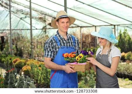 Female and male gardeners with a basket full of flower pots posing in a hothouse - stock photo