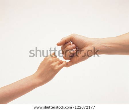 Female and male hands reconcile with clasping each others little finger