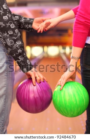 Female and male hands with balls in bowling club; man and woman holding hands - stock photo