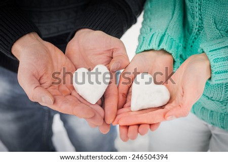 Female and male hands with snow hearts  Love concept. Valentine's Day - stock photo