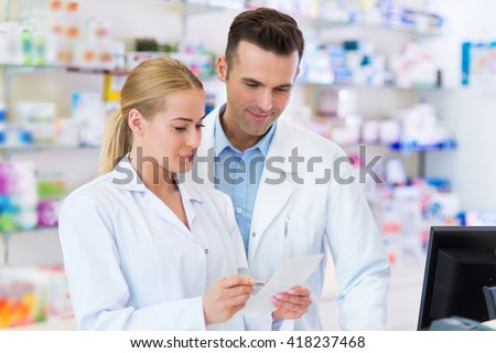Female and male pharmacists in pharmacy - stock photo