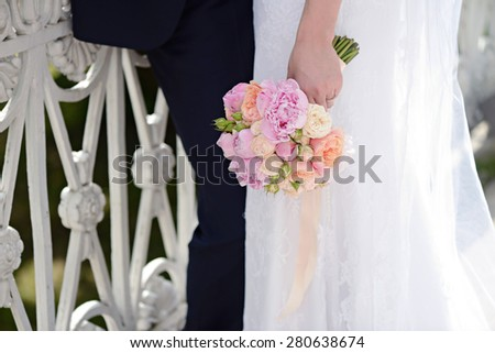 Female and male portrait with bouquet. Wedding couple. Beautiful sexy model girl in white dress. Man in suit. Beauty bride with groom. Woman in bridal gown. Cute lady and guy outdoors - stock photo