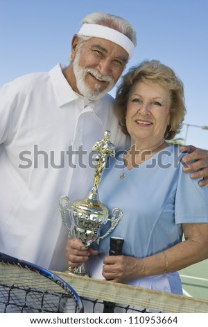Female and male senior tennis player holding trophy after winning - stock photo