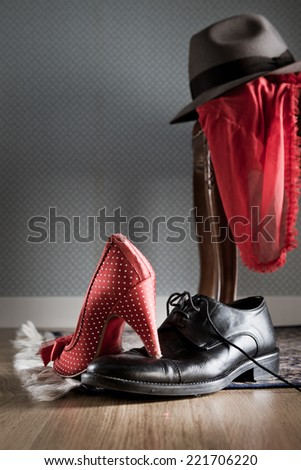 Female and male shoes, lingerie and male hat on chair and floor, romance and sensuality concept. - stock photo