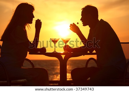 Female and man's silhouettes on sunset sit at table with two glasses and olives outdoor - stock photo