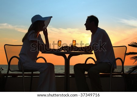 Female and man's silhouettes on sunset sit at table with two glasses outdoor - stock photo