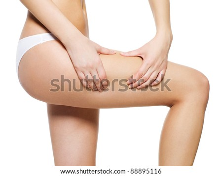 Female applying cosmetic cream from cellulite on leg - isolated on white