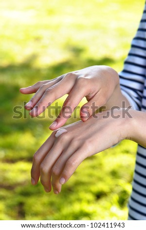 Female applying cream to her hands in park