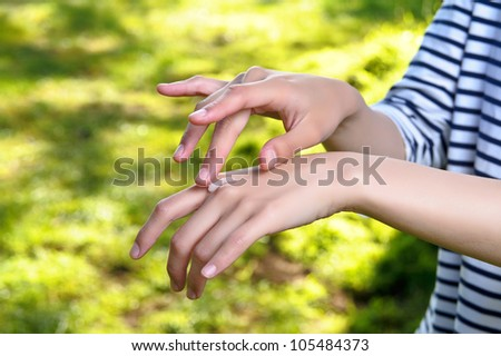 Female applying cream to her hands in the park