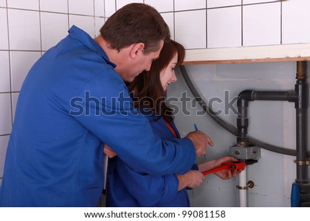female apprentice plumber and male instructor - stock photo