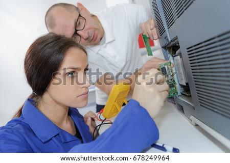 female apprentice repairing machine