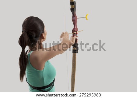 Female archer practicing archery against gray background - stock photo