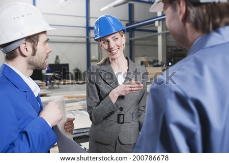 Female architect and foremen in industrial hall - stock photo