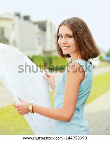 Female architect at a construction standing with folder near house