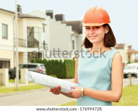 Female architect at a construction standing with folder near house - stock photo