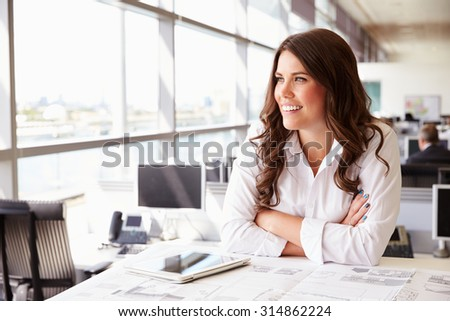 Female architect at her desk in an office, looking away - stock photo