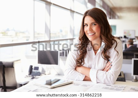 Female architect at her desk in an office, looking to camera - stock photo