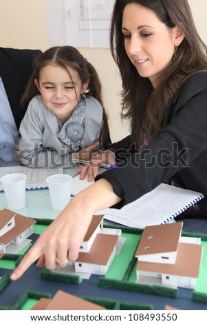female architect in office with little girl pointing at model - stock photo