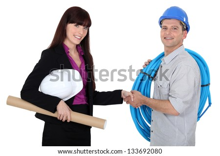 Female architect shaking electrician's hand - stock photo