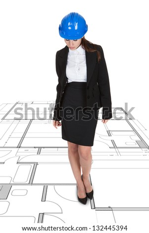 Female Architect Standing Over Blueprint On White Background - stock photo