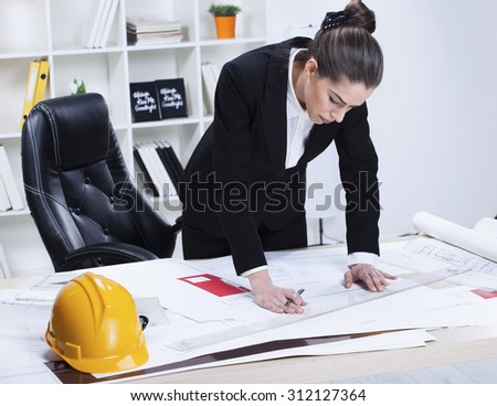 Female Architect Studying Plans In Office. Woman architect working in her office