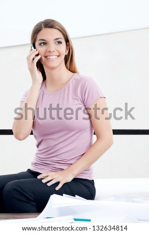 Female architect using cell phone with blueprints. - stock photo