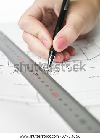 Female architect working on a blueprint, close up on hand and blueprint.