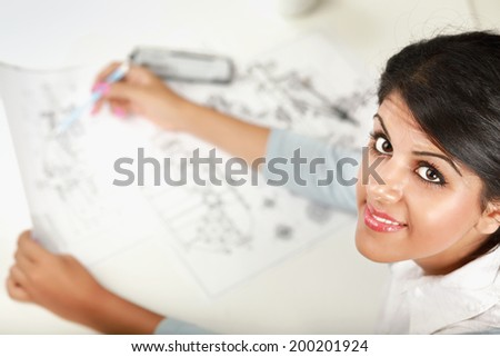Female architect working with blueprints at office desk - stock photo