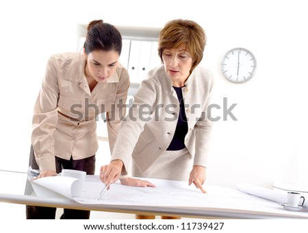 Female architects designing on blueprint at office. - stock photo