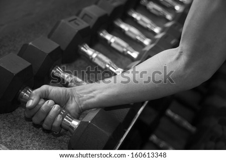 Female Arm Gripping Weights - stock photo