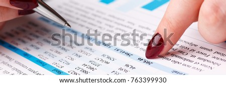 Female arm hold and point silver pen in financial graph