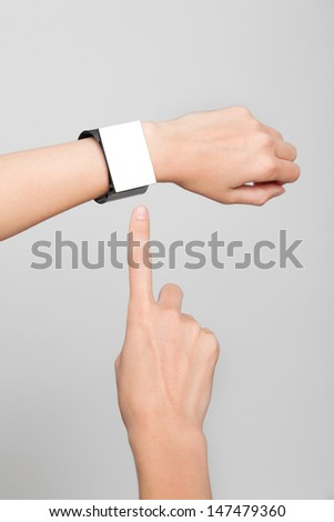 Female arm with a modern Internet Smart Watch on grey background. The Screen is blank and you can insert everthing you want to it. - stock photo