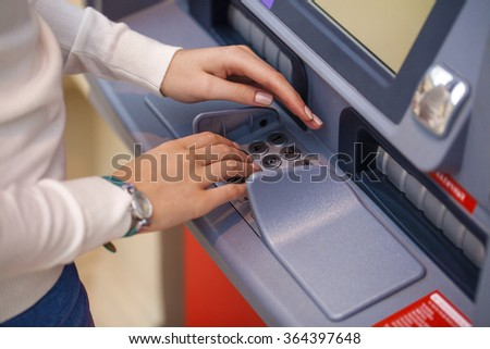 Female arms, ATM - entering pin   - stock photo