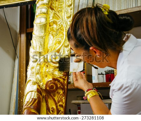 Female artisan decorating a big wooden picture frame.Application of gold leaf. Focus on the tool. Lomo effect. - stock photo