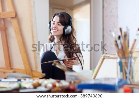 Female artist in headphones paints picture on canvas with oil paints  - stock photo
