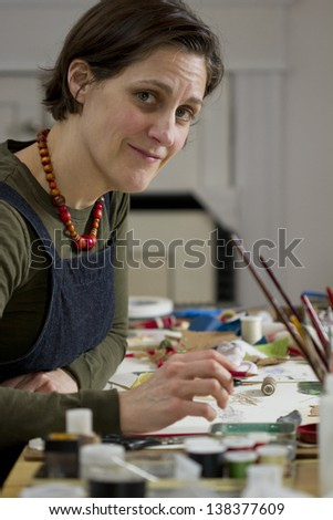 Female Artist in her studio smiling to the camera