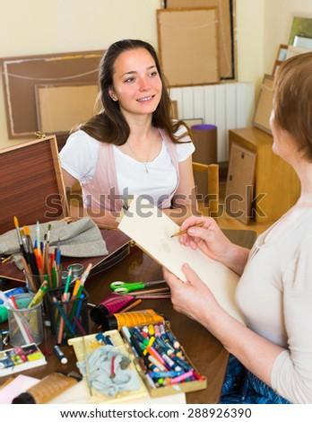 Female artist painting portrait of smiling longhaired girl in art studio - stock photo