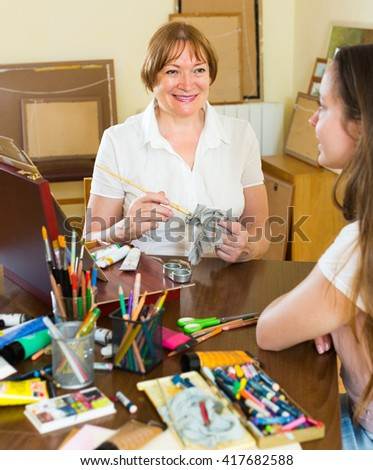 Female artist painting portrait of young girl at art studio with pencil and paints - stock photo