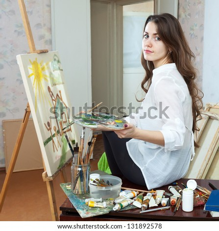 Female artist paints picture on canvas with oil paints in her stidio - stock photo