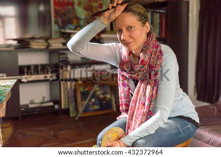 Female artist pausing to wipe her forehead with a paintbrush in her hand as she sits back to analyse a canvas she is working on on an easel in an art studio or gallery - stock photo